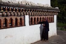 Woman spinning the prayer wheels of Chorten Lhakhang. Paro, Bhutan. - Photo #24341