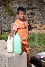 Boy filling jugs with water. Phobjikha Valley, Bhutan. - Photo #23743