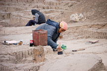Woman brushing dirt during an excavation at Huaca Pucllana, an adobe pyramid. Lima, Peru. - Photo #8744