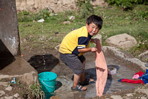 Boy washing clothes. Phobjikha Valley, Bhutan. - Photo #23746