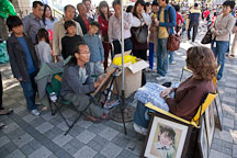 An artist draws a pastel portrait of a tourist outside N Seoul Tower, gathering a crowd. - Photo #20654