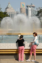 Two women chatting by the fountain. Hong Kong Park, China. - Photo #16454