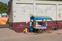 Young woman and child running with a vegetable stand. Puerto Maldonado, Peru. - Photo #9059
