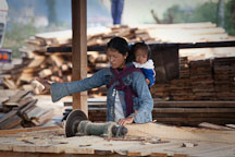 Woman with baby sawing lumber. Paro, Bhutan. - Photo #24369