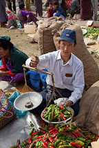 Man weighing chili peppers for sale at the weekend market. Punakha, Bhutan. - Photo #23307