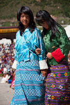 Two teenage girls dressed in traditional kiras at the Thimphu tsechu. Bhutan. - Photo #22472