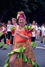 Woman dressed in orange and green wearing a hat made of fruits. Carnaval's grand parade. San Francisco. - Photo #1086