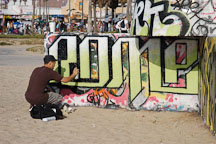 Man spray painting a wall with his inscription. Venice, California, USA. - Photo #7462