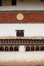 The outer walls of Chimi Lhakhang are lined with prayer wheels. Lobesa Valley, Bhutan. - Photo #23597